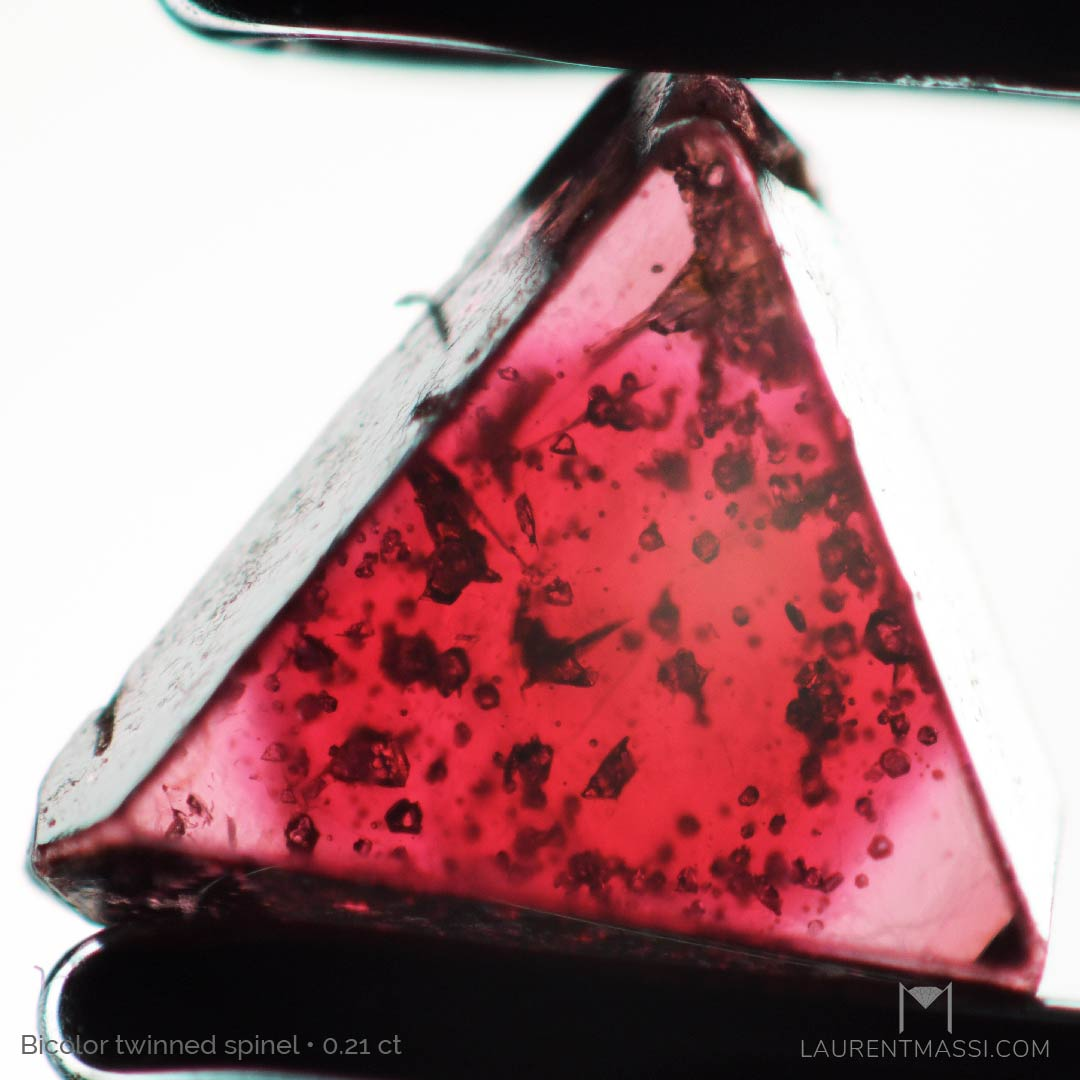 Photomicrography of natural near colorless spinels (0.21 ct) with a spherical bright red core